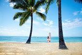 Woman Surfer on Tropical Paradise Beach