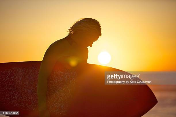 Woman surfer silhouetted in sunset