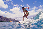 Woman surfing on ocean wave, low angle view