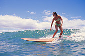 Woman surfing on ocean wave