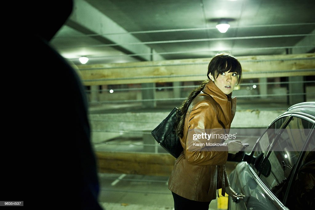 woman surprised by hooded man in parking garage