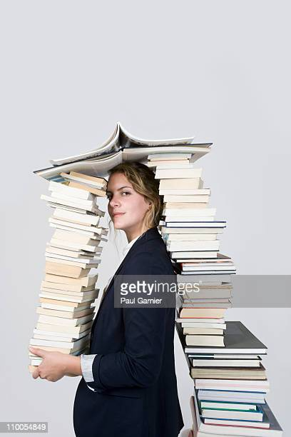 Woman surrounded by books looking at camera