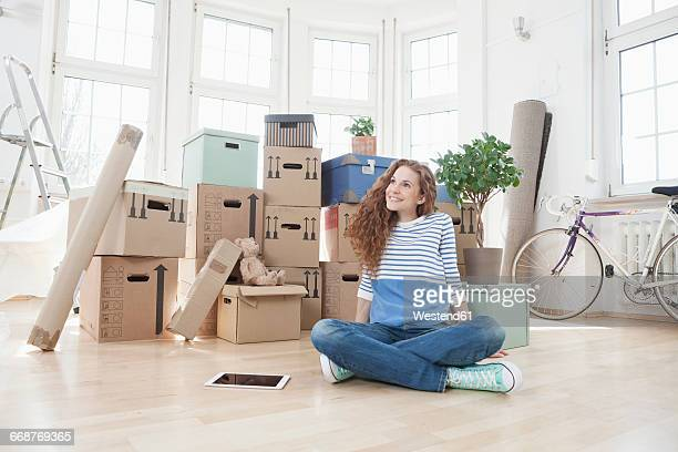 Woman surrounded by cardboard boxes sitting on floor