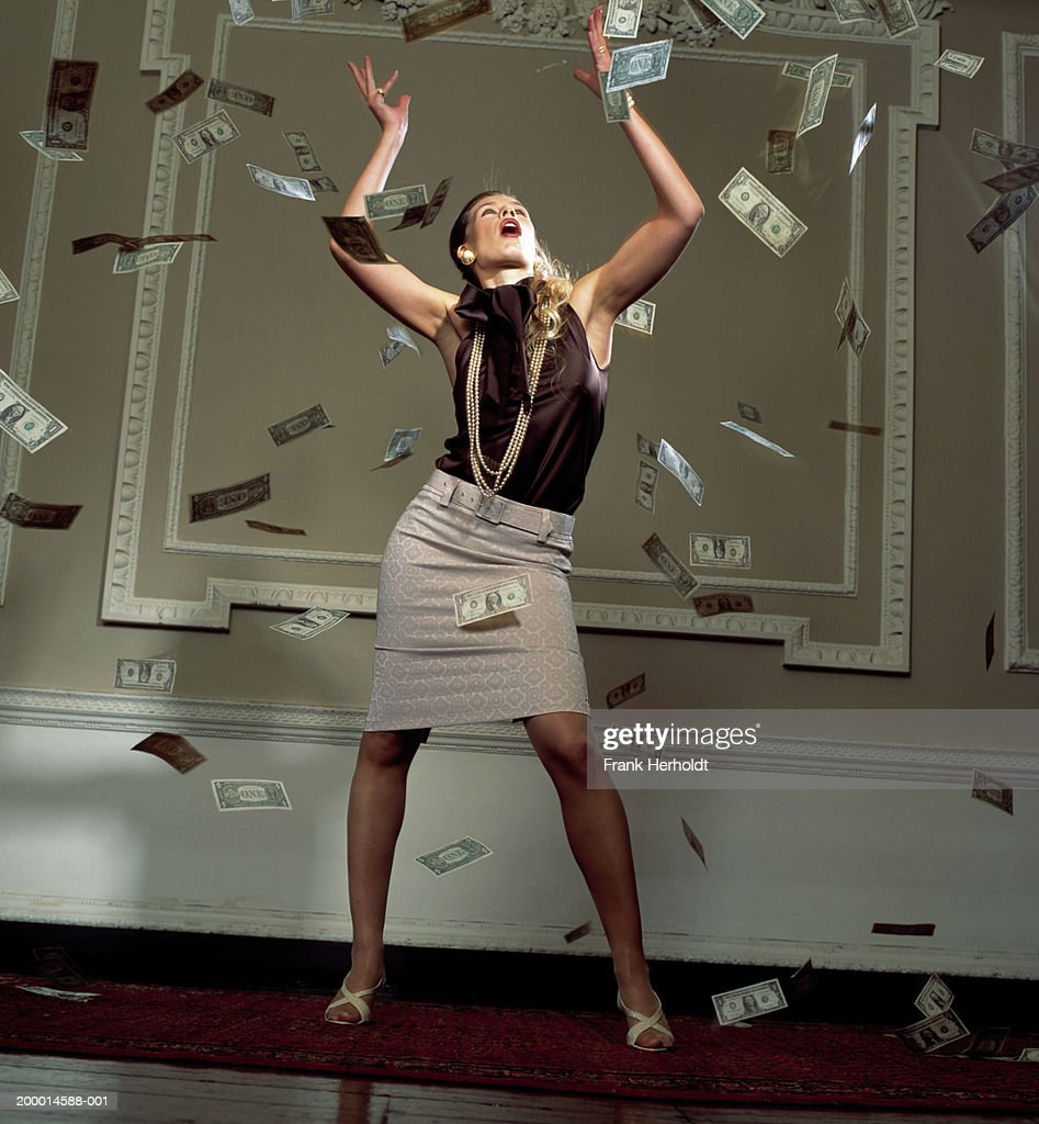 Woman surrounded by falling banknotes