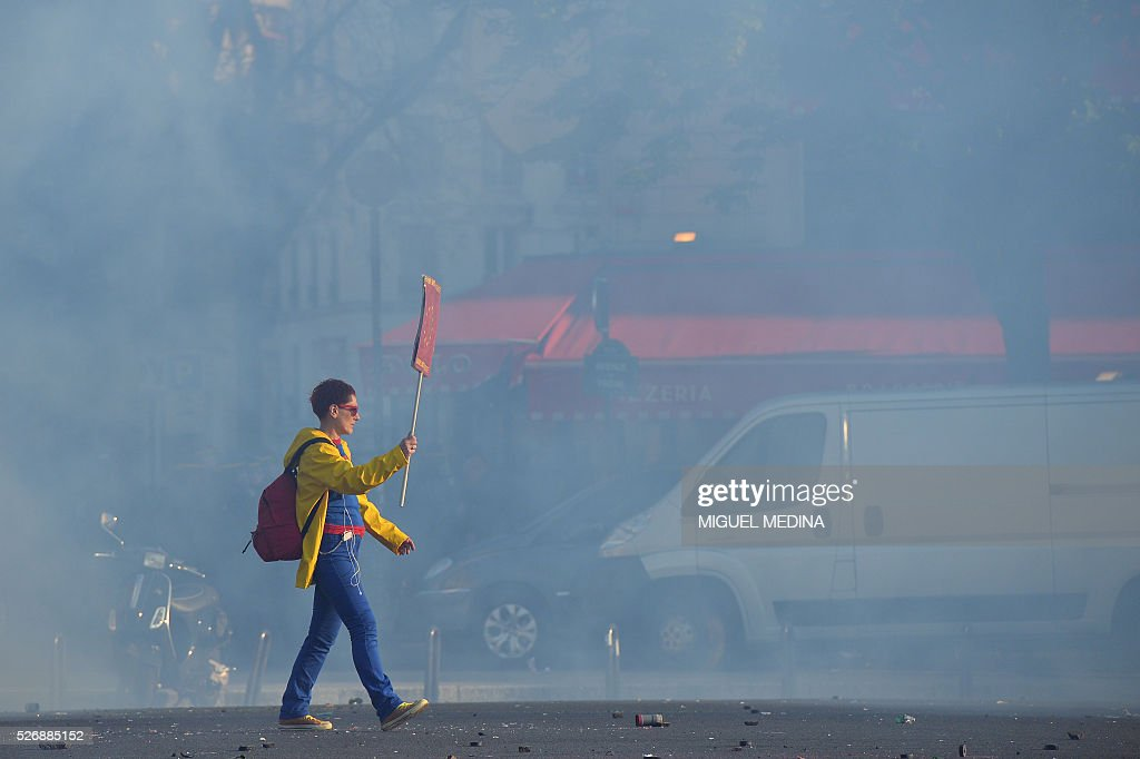A woman surrounded by smoke holds a placard during the traditional May Day demonstration in Paris on May 1, 2016.