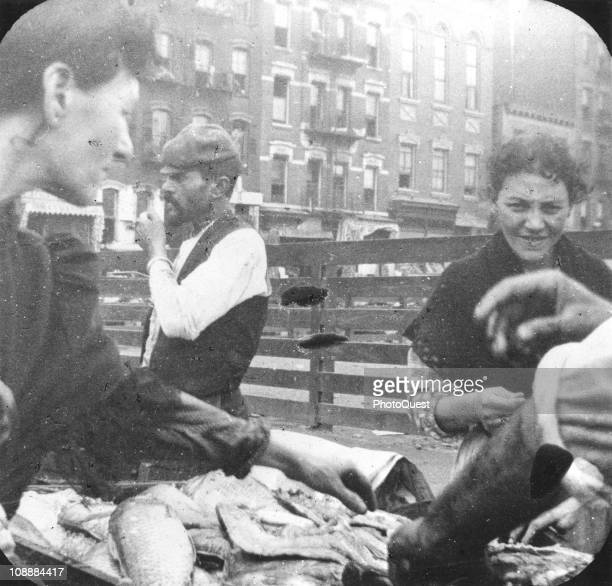 A woman surveys the wares of an Italian push cart selling fish in a crowded street scene probably in New York's Lower East Side neighborhood late...