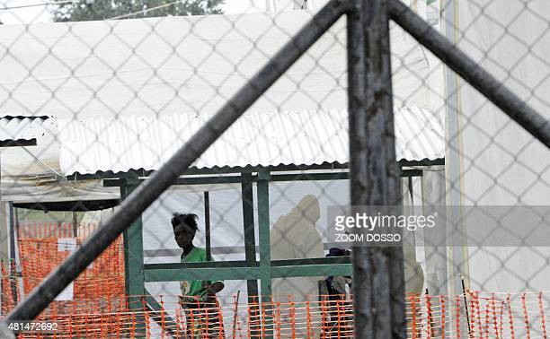 A woman suspected of carrying ebola looks on while under quarantine in the red zone of the Elwa clinic an ebola treatment center in Monrovia on July...