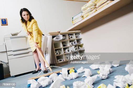 Woman sweeping crumpled up paper : Stock Photo