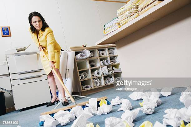 Woman sweeping crumpled up paper