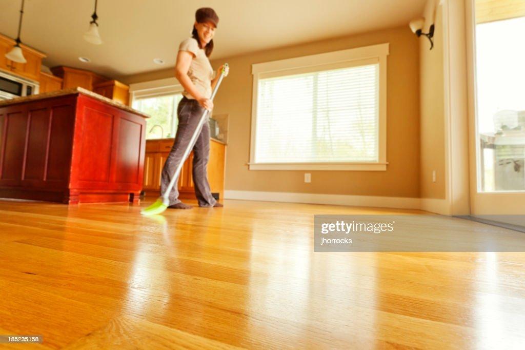 woman sweeping hardwood floor with broom