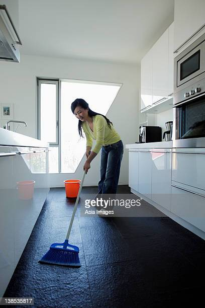Woman sweeping her kitchen floor