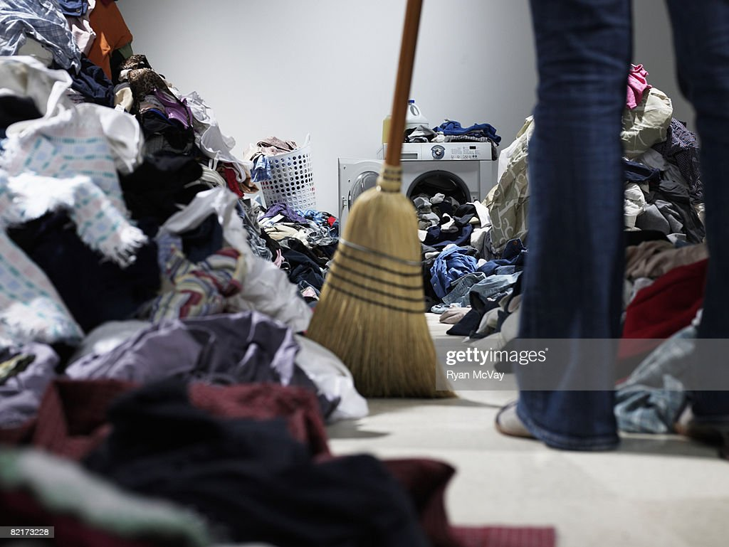 Woman sweeping pathway through piles of laundry : Stock Photo