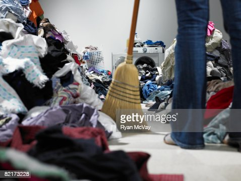 Woman sweeping pathway through piles of laundry : Stock-Foto