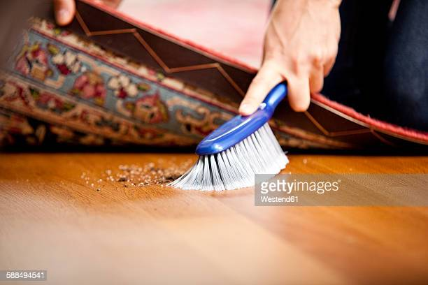 Woman sweeping under the carpet
