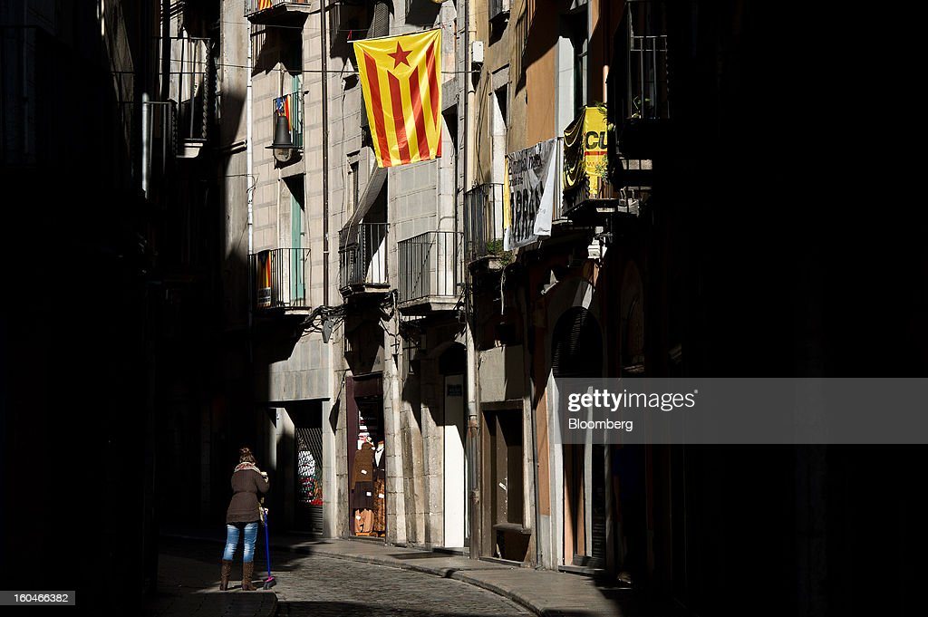 A woman sweeps a street beneath a pro-independence Catalan flag hanging from a nearby residential building in Girona, Spain, on Thursday, Jan. 31, 2013. Spain's recession deepened more than economists forecast in the fourth quarter as the government's struggle to rein in the euro region's second-largest budget deficit weighed on domestic demand. Photographer: David Ramos/Bloomberg