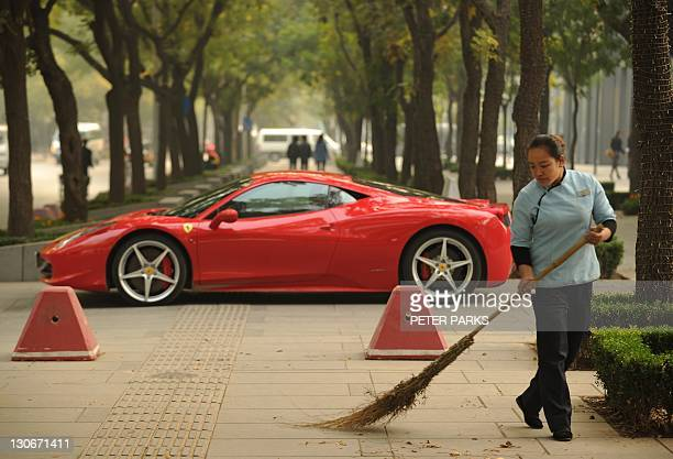 A woman sweeps leaves in front of a new Ferrari 458 Italia in Beijing on October 28 2011 The head of the European bailout fund dampened hopes October...