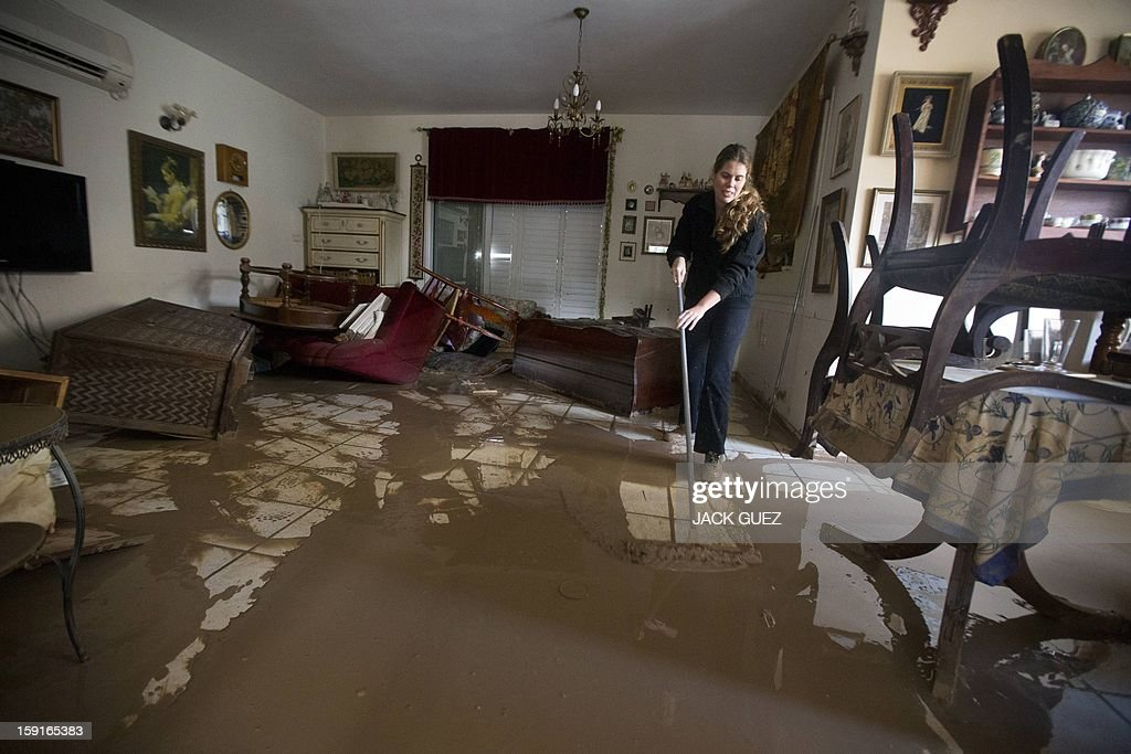 A woman sweeps murky water from her flooded house in Beit Hefer near the Mediterranean coastal city of Netanya, north of Tel Aviv, on January 9, 2013, after heavy rains overnight. Israel and the Palestinian territories have been lashed by heavy rain and high winds since January 6, which has caused flooding across the region. AFP PHOTO / JACK GUEZ
