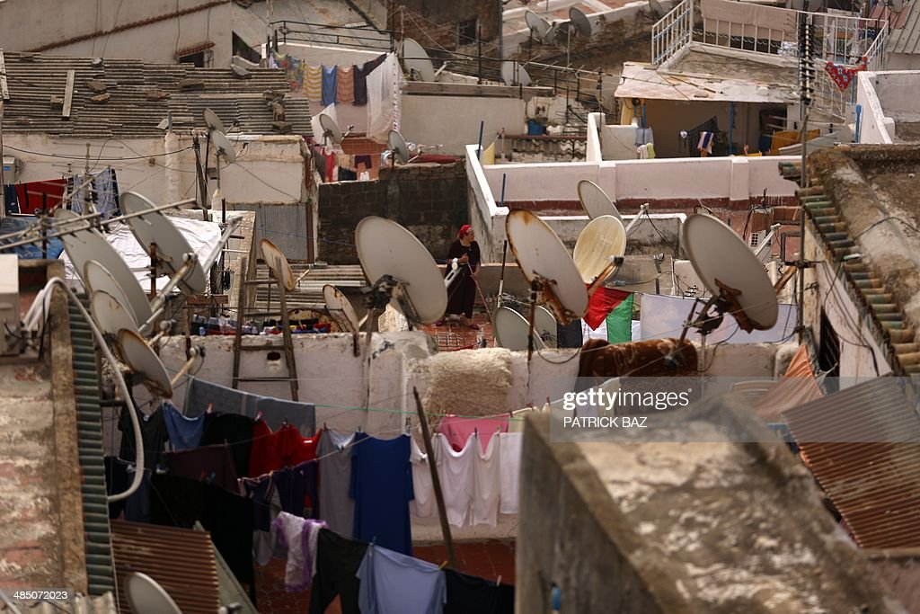 A woman sweeps on a rooftop of a house between hanging laundry in the old town of Algiers, known as the 'Kasbah',on April 16, 2014. AFP PHOTO/PATRICK BAZ