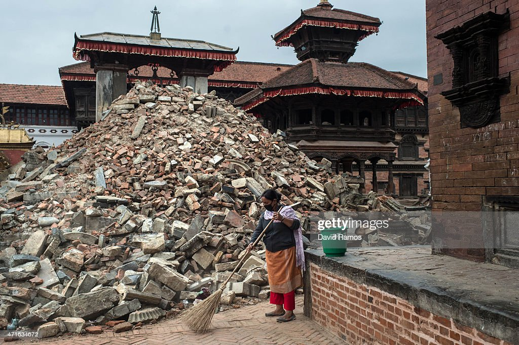 A woman sweeps the street next to debris of a collapsed temple at Durbar square in Bhaktapur on April 30 2015 in Kathmandu Nepal A major 78...