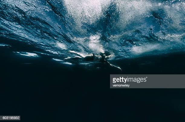 Woman swimming across deep dark water underwater