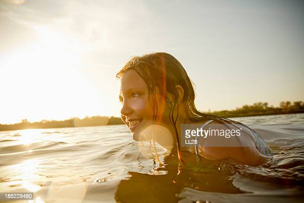 A woman swimming in a lake as sunset approaches