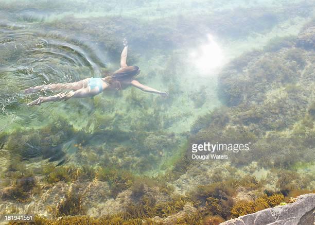 Woman swimming in idyllic rock pool.