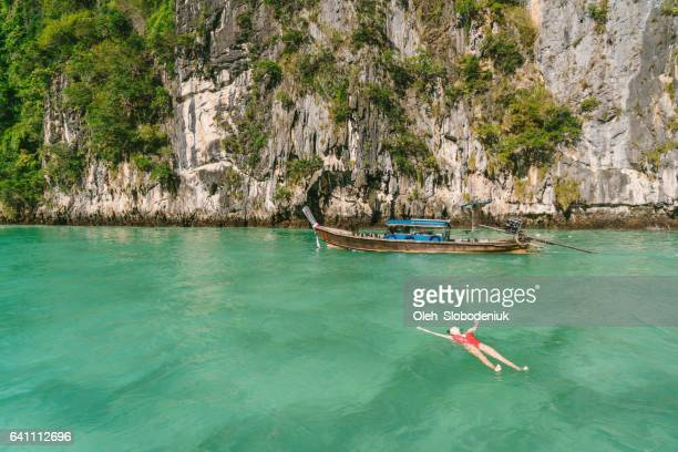 Woman  swimming near the Thai Taxi Boat