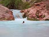 Woman swimming in the turquoise waters of Havasu Creek, Grand Canyon.