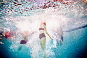 Woman swimming to surface of pool underwater view