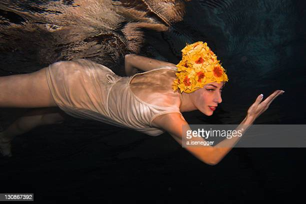 woman swimming under water with vintage clothes