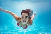 Beautiful woman swimming underwater in pool. Female swimmer in bikini at holiday resort.