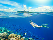 Woman swims around a coral reef surrounded by a multitude of fish on the background Islands.