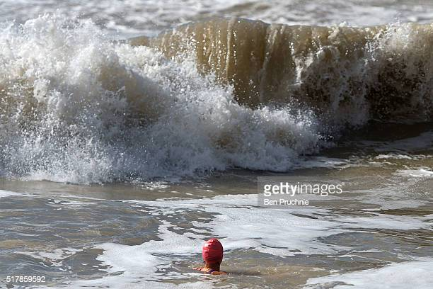 A woman swims in the waves on Brighton Beach on March 28 2016 in Brighton England Yesterday the Met Office issued an amber warning for winds for...