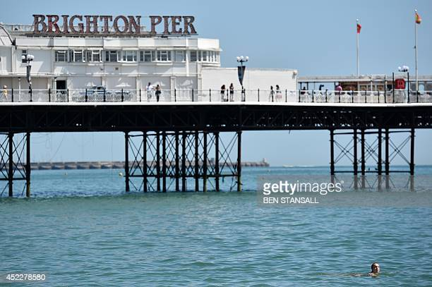 A woman swims past Brighton Pier in Brighton Sussex on July 17 2014 AFP PHOTO/BEN STANSALL