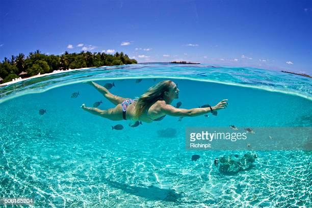 Femme nage avec poissons tropicaux dans un lagon