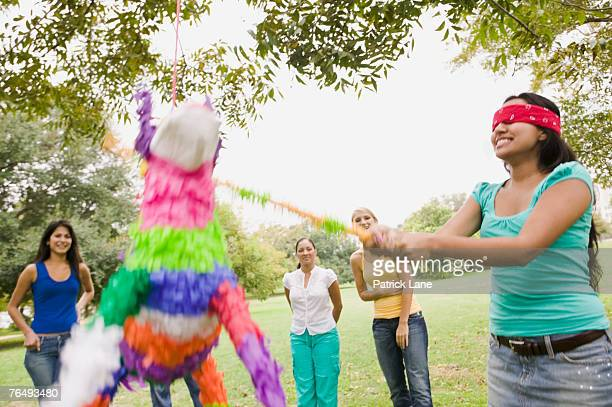 Woman swinging at a pinata