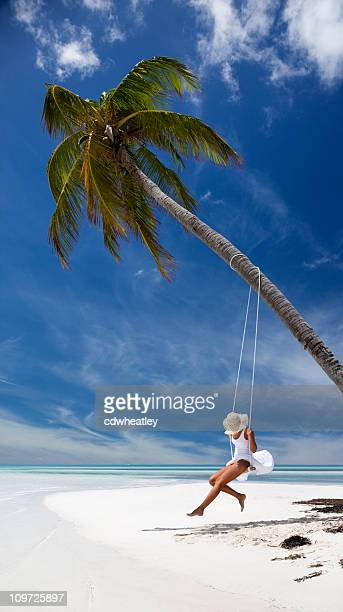 woman swinging from a palm tree on tropical beach