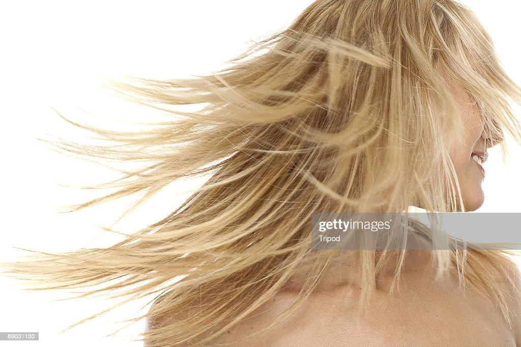 Woman swinging hair, smiling : Stock Photo
