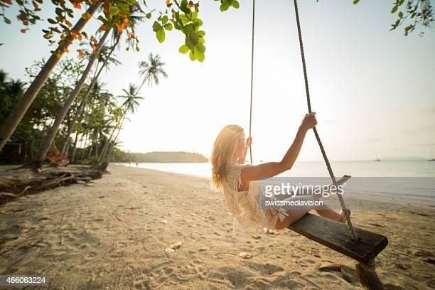 Frau schwingen auf seasaw – Sonnenuntergang am Strand
