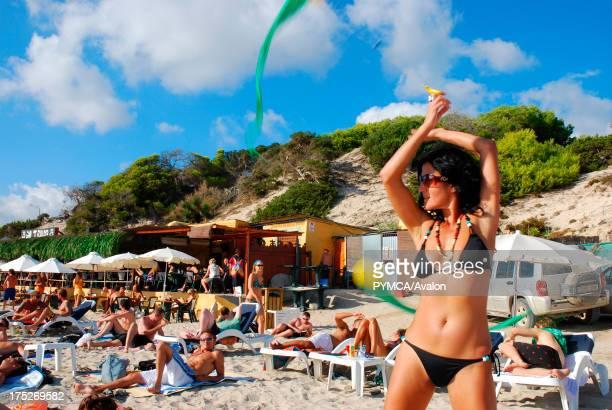 A woman swinging Poi Poi streamers Sa Trincha bar Las Salinas beach Ibiza