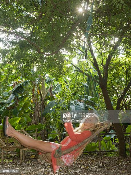 Woman swings on a rope chair in the jungle