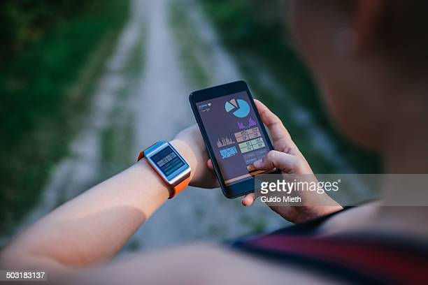 Woman synchronising smartwatch and mobile phone.