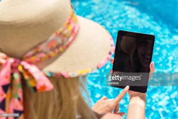 Femme & comprimé au bord de la piscine