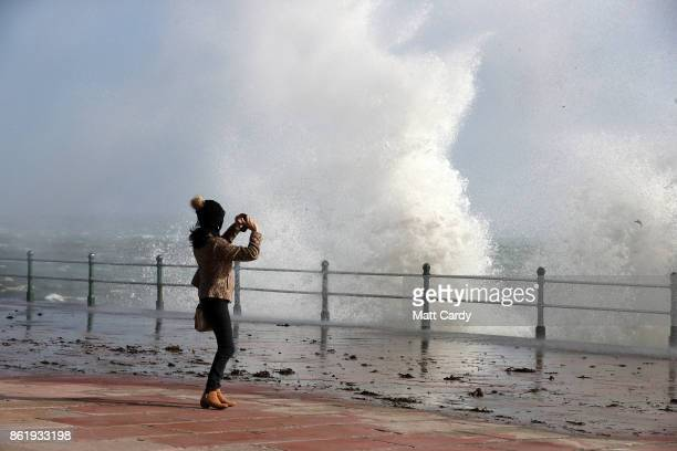 A woman take a photograph as waves crash up onto Penzance seafront on October 16 2017 in Cornwall England The hurricane comes exactly 30 years after...