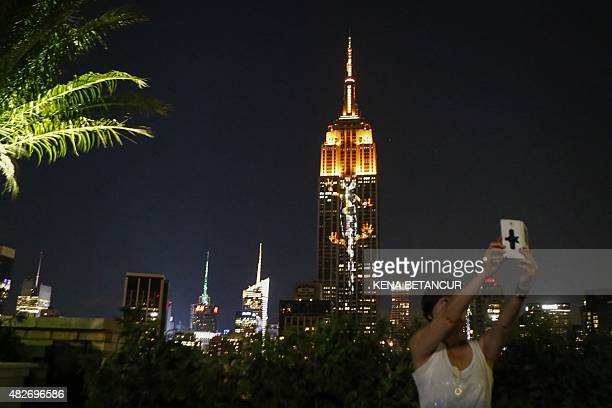 A woman take a selfie in front of projections on the Empire State Building in the 'Projecting Change on the Empire State Building' project made by...