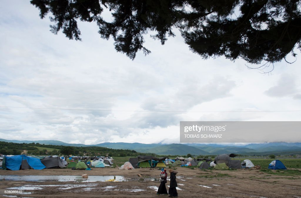Woman take a walk through at a makeshift camp for migrants and refugees near the village of Idomeni not far from the Greek-Macedonian border on May 4, 2016. Some 54,000 people, many of them fleeing the war in Syria, have been stranded on Greek territory since the closure of the migrant route through the Balkans in February. / AFP / TOBIAS
