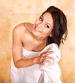 Young woman take bubble  bath. Girl happily wipes hair towel