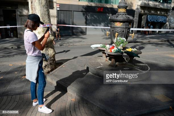 A woman take pictures of flowers displayed at the Canaletas fountain on the Rambla boulevard on August 18 a day after a van ploughed into the crowd...