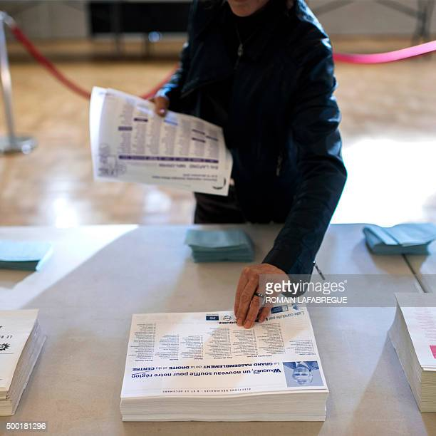 A woman takes a ballot of chief candidate of the rightwing party Les Republicains Laurent Wauquiez before voting in regional elections for the...