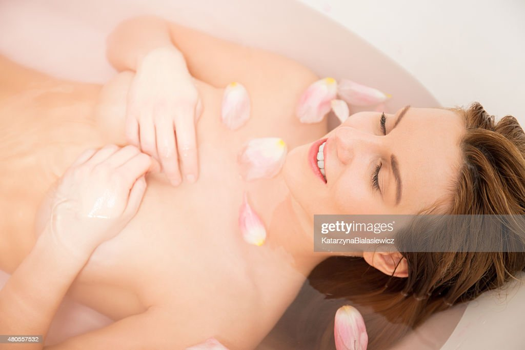 Woman takes a bath with rose petals : Stock Photo